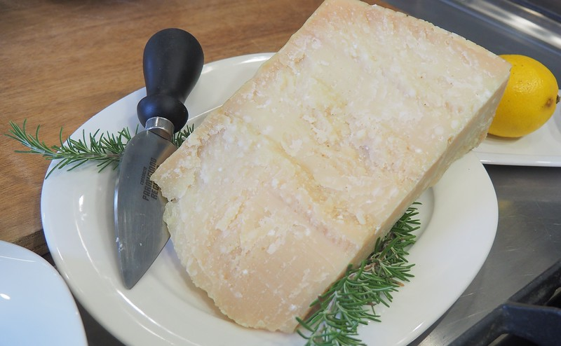 A big chunk of Parmigiano-Reggiano cheese with a knife beside it