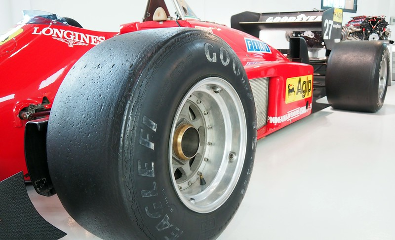 A close-up shot of one of the wheels of a racing car on display at the Enzo Ferrari Museum