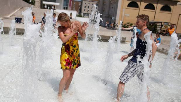 Tourists cool down at a fountain on a hot summer day in downtown Rome.