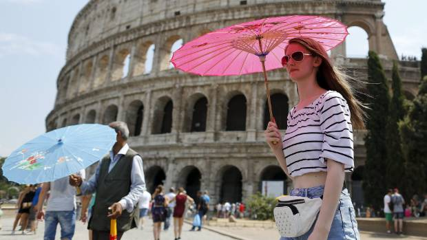People use umbrellas to protect themselves from the sun in front of Colosseum during a hot summer day.