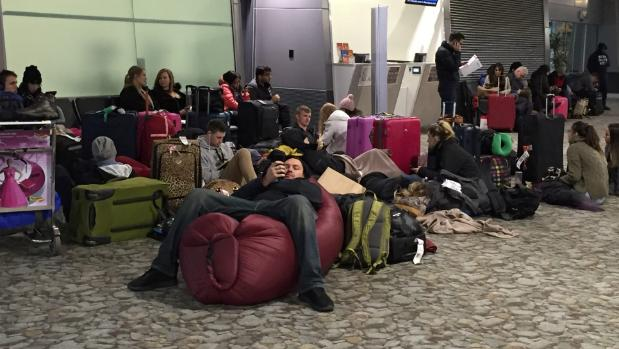 People wait at Wellington Airport as flights are delayed due to the storm.