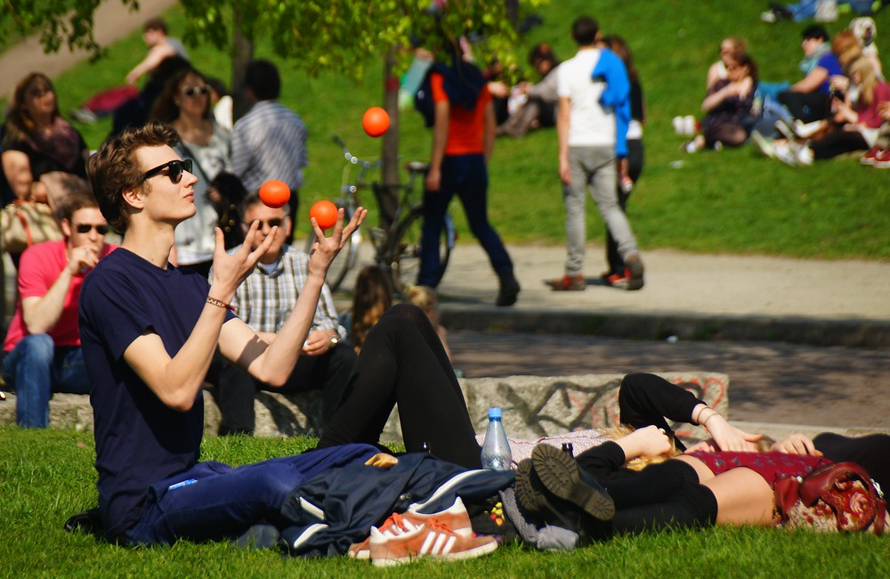 Young man wearing sunglasses and juggling balls while sitting down in Mauerpark, in Berlin, Germany.