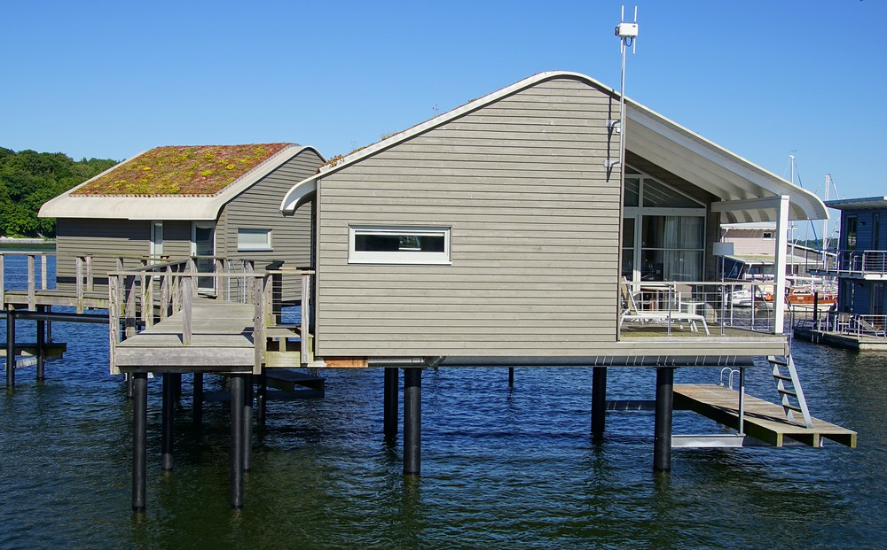 Cool stilt-house apartments for rent with scenic views and open door access to the water on Ruegen Island, Germany.