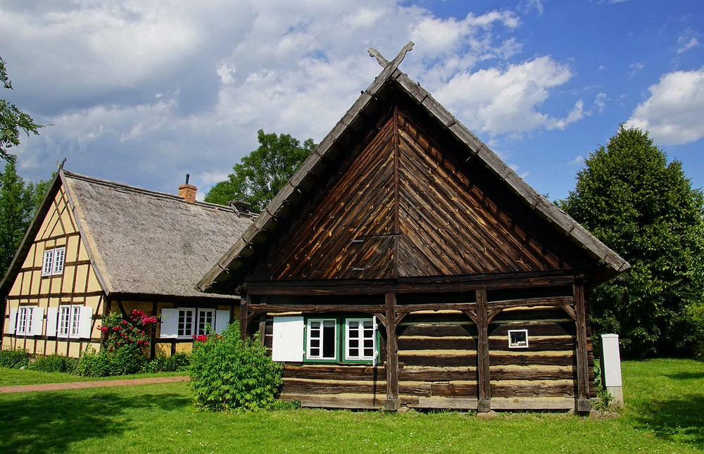 You can easily find this type of traditional architecture (thatched roof) in Spreewald, Germany.