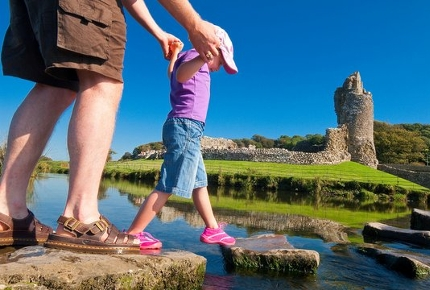 Navigate stepping stones in a river to reach Ogmore Castle